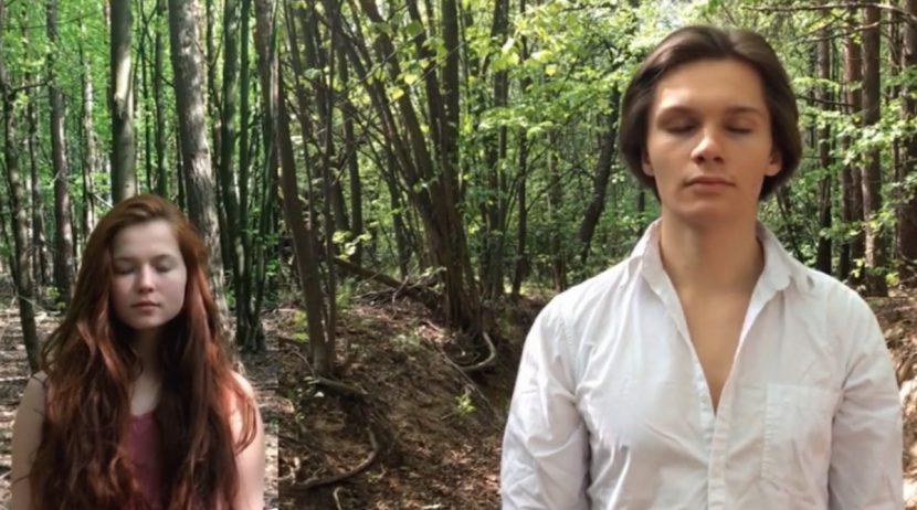 Scena z filmu - dwoje aktorów, dziewczyna i chłopak, stoją na tle lasu z zamkniętymi oczami.